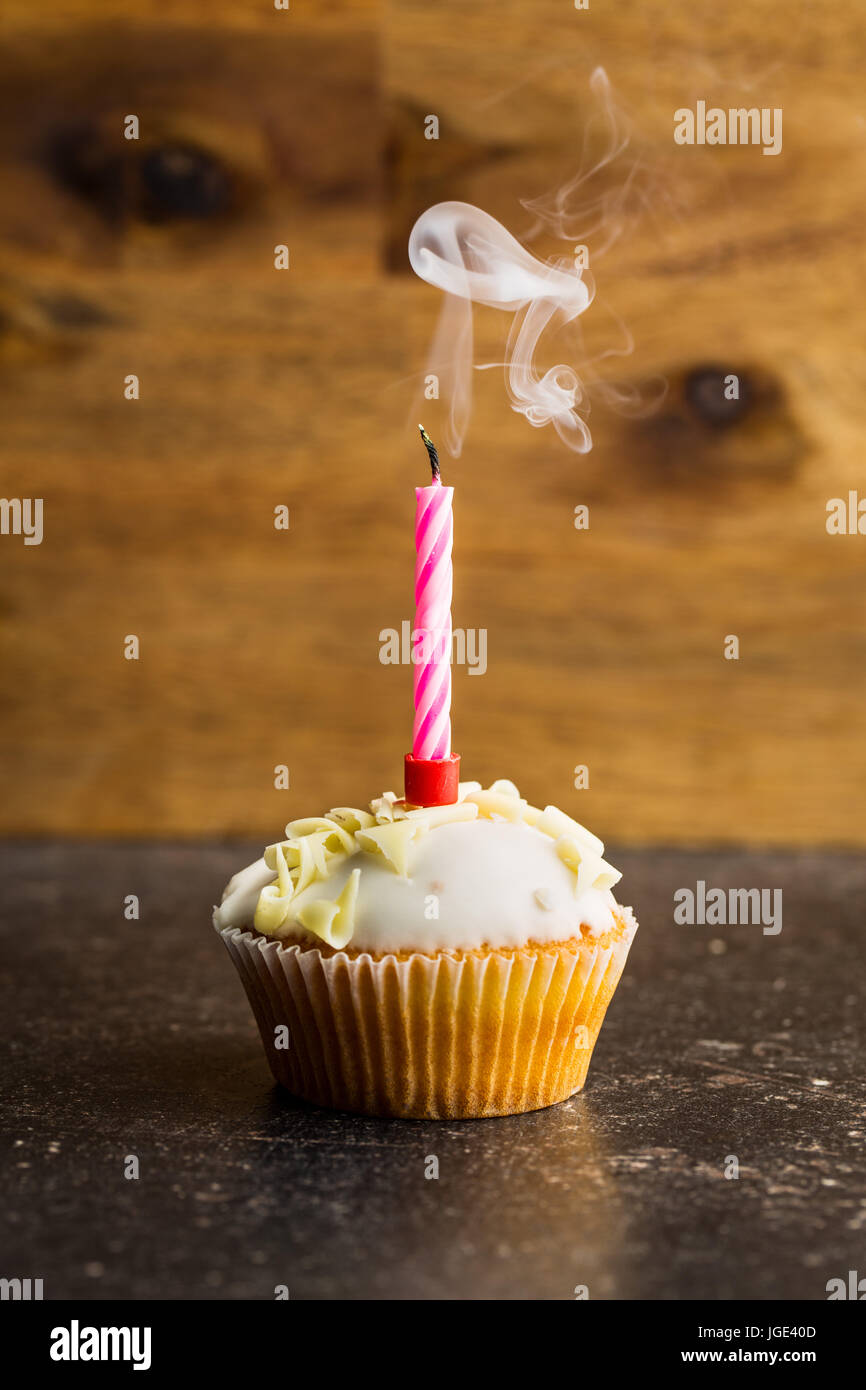 Cupcake with a candle blown on table. - Stock Image