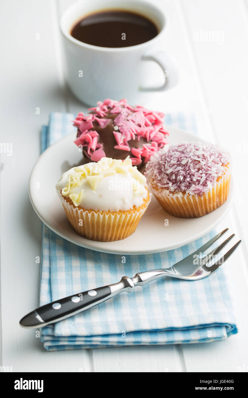 Tasty sweet cupcakes on kitchen table. - Stock Image