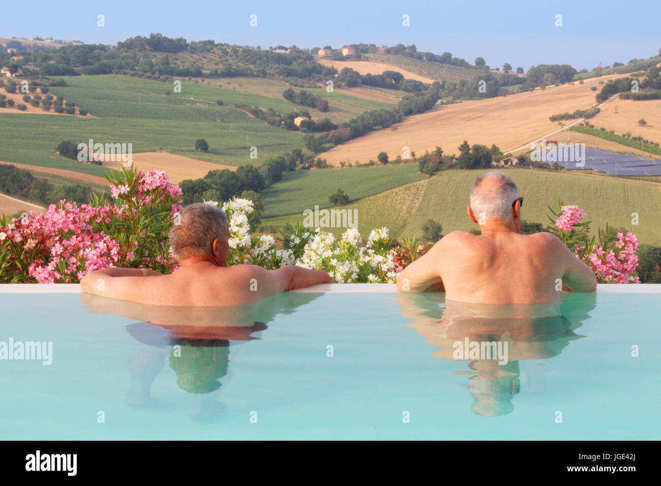 Mature men relaxing by the pool - Summer vacation - Stock Image