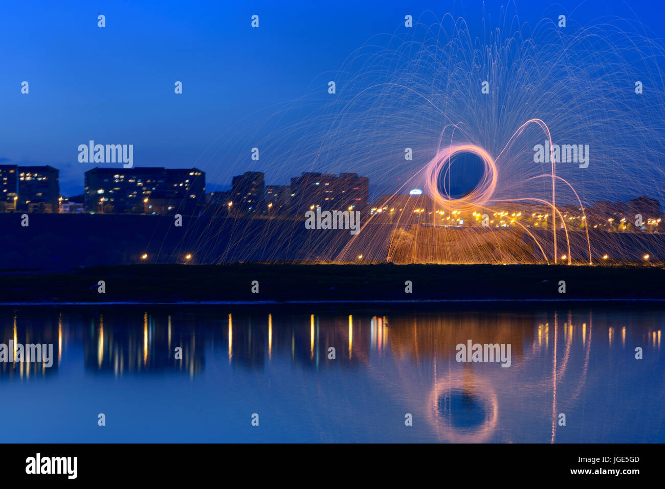 Hot Golden Sparks Flying from Man Spinning Burning Steel Wool near River with Water Reflection. Long Exposure Photography Stock Photo