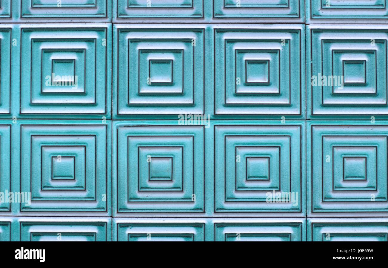 Old tiles on the wall with a unique square pattern, turquoise color ...