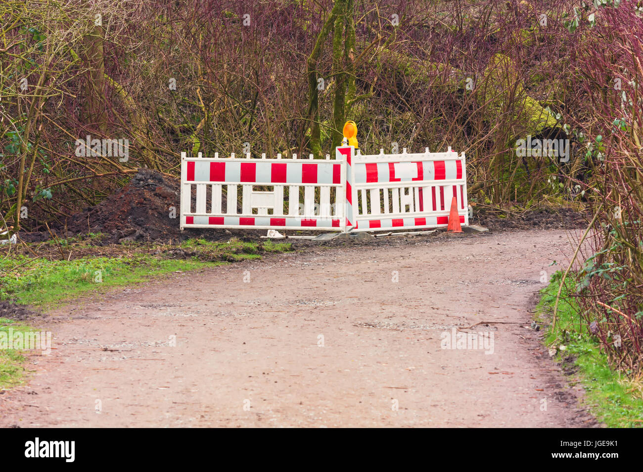 Red and White Street Barricade. Road block or construction site barrier on a road. - Stock Image
