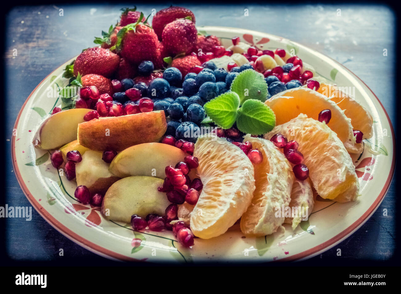 A closeup view of a platter of mixed fruits including strawberries, oranges, blueberries, apples and bananas - Stock Image