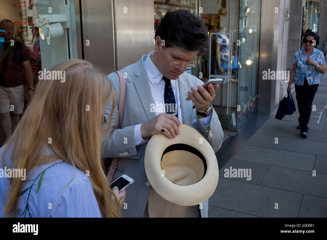 A gentleman checks his messages after removing his summer hat, on 5th July 2017, in London, England. - Stock Image
