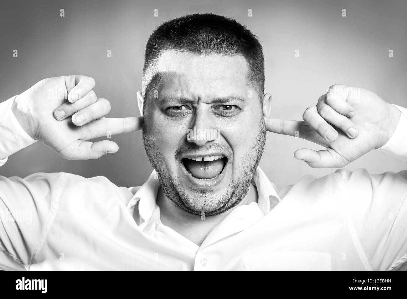 Stressful unpleasant situation conflict. Angry mad young man plug closing ears with fingers, protecting from loud - Stock Image