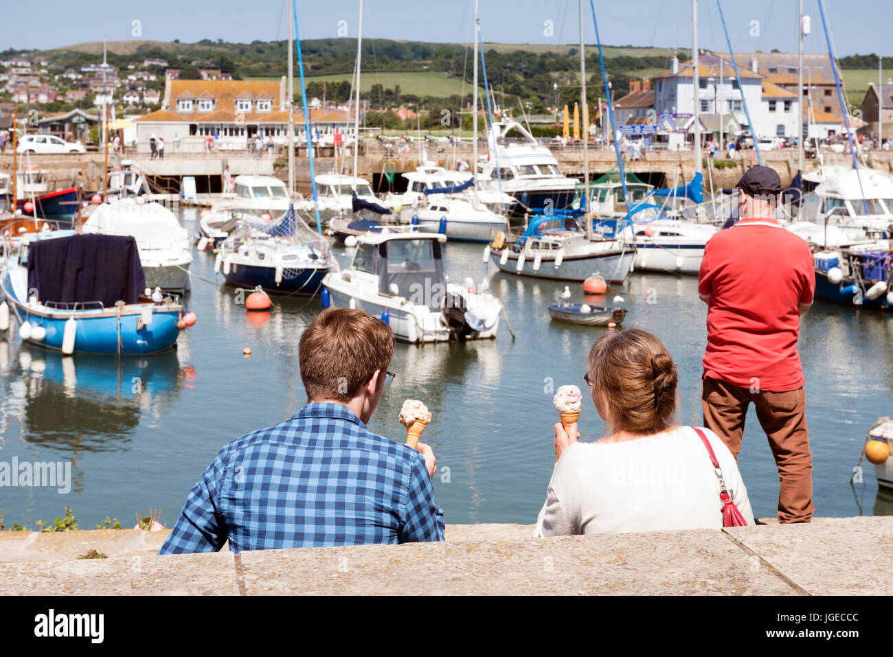 People eating ice creams overlooking the harbour at West Bay, Dorset, UK. - Stock Image