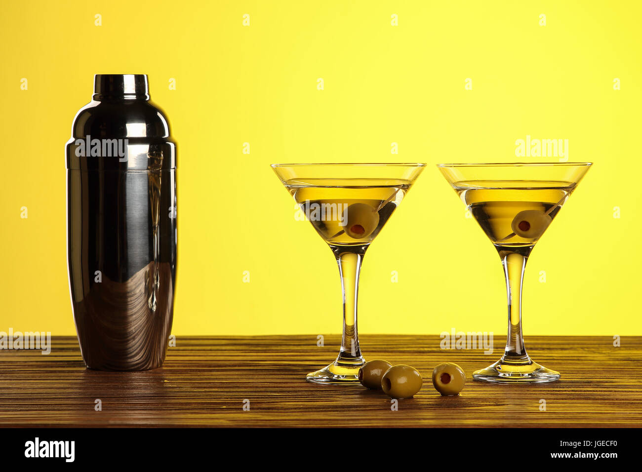 Two cocktails in martini glasses with green olives and shaker on a wooden surface against yellow background with Stock Photo