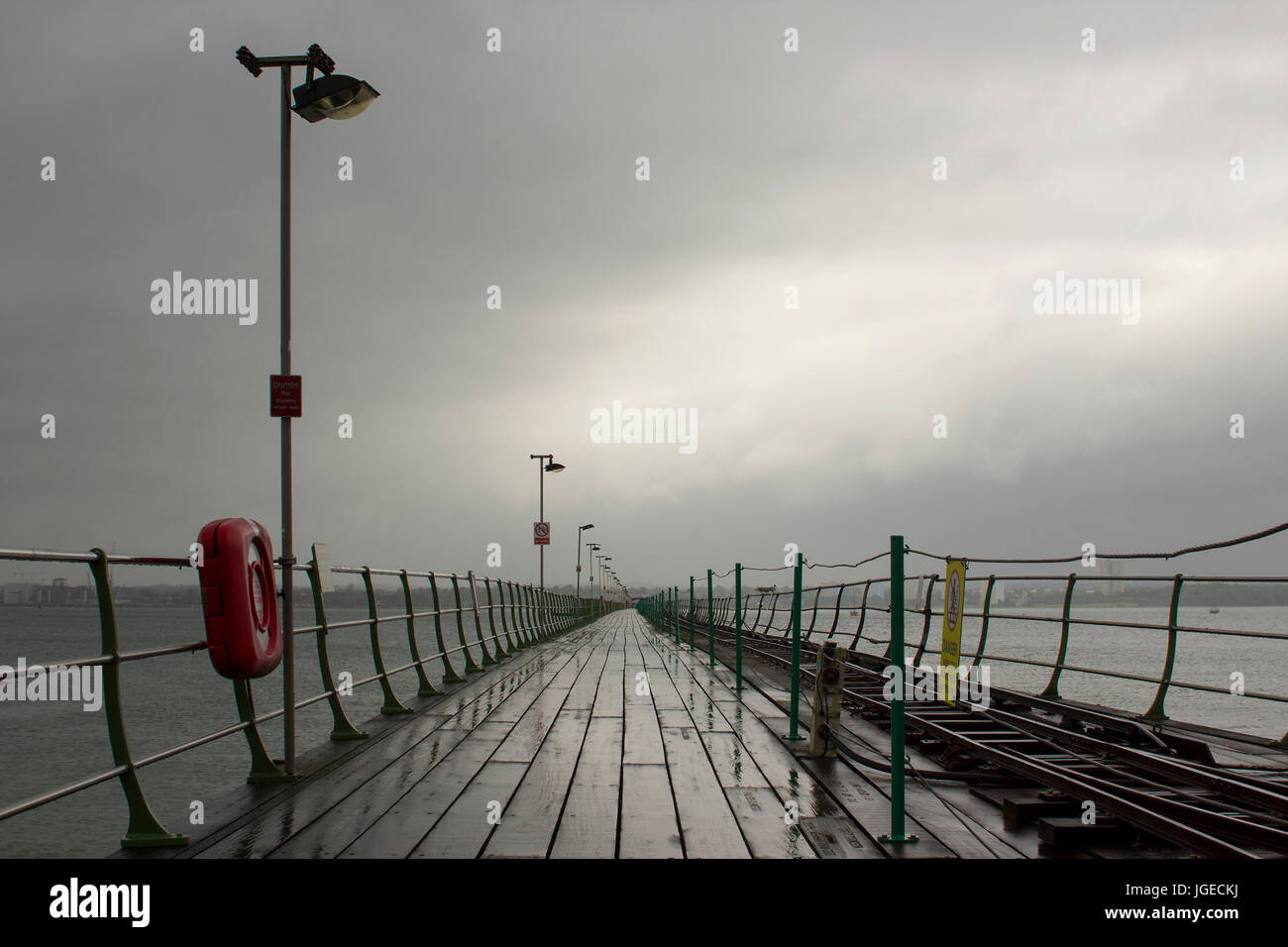 The long pier at Hythe in the south of England with its wooden walkway and railway line to the Southampton Ferry - Stock Image