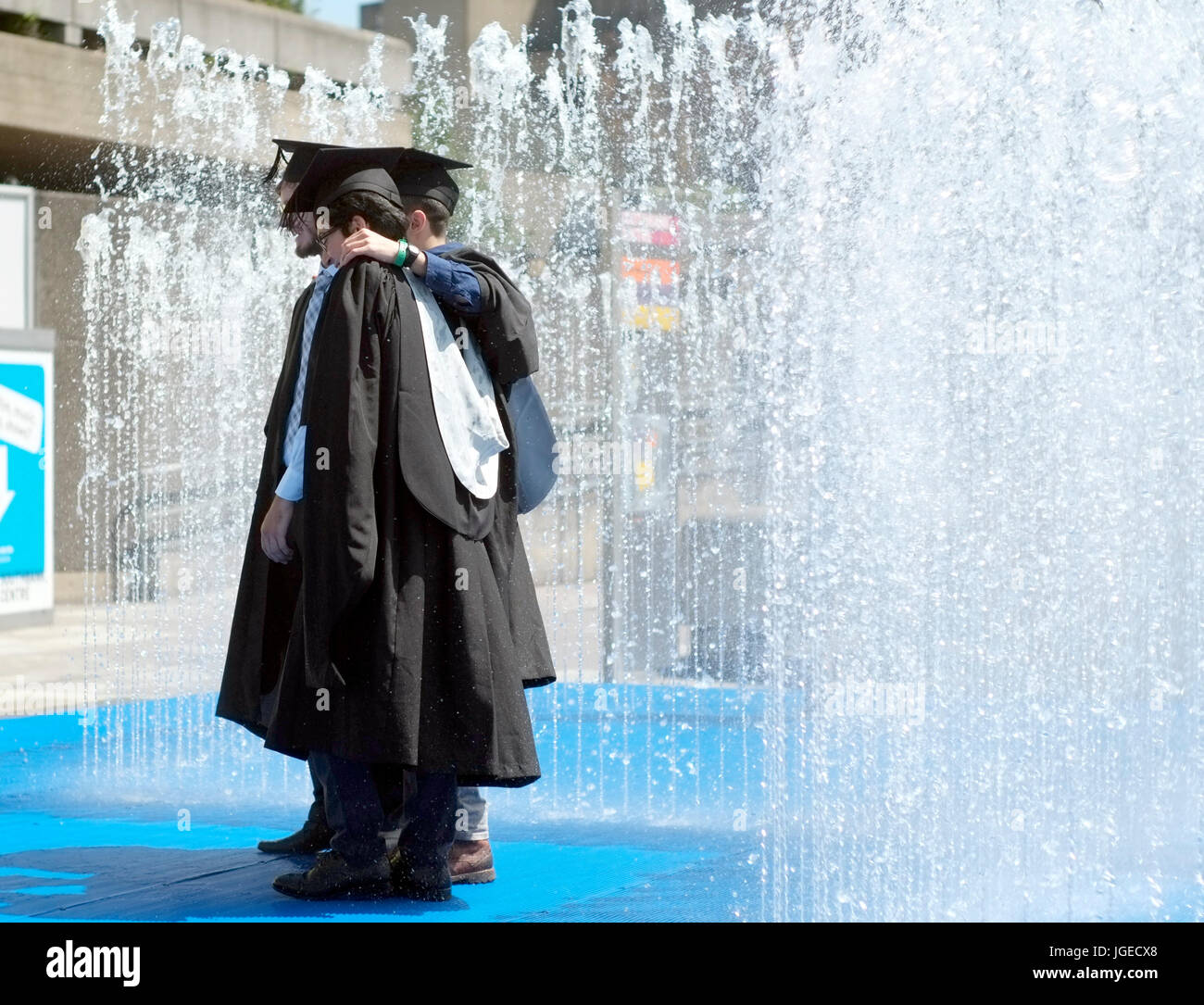 Graduates stand in a fountain, on a sunny day, after receiving their certificates in the Royal Festival Hall, on Stock Photo
