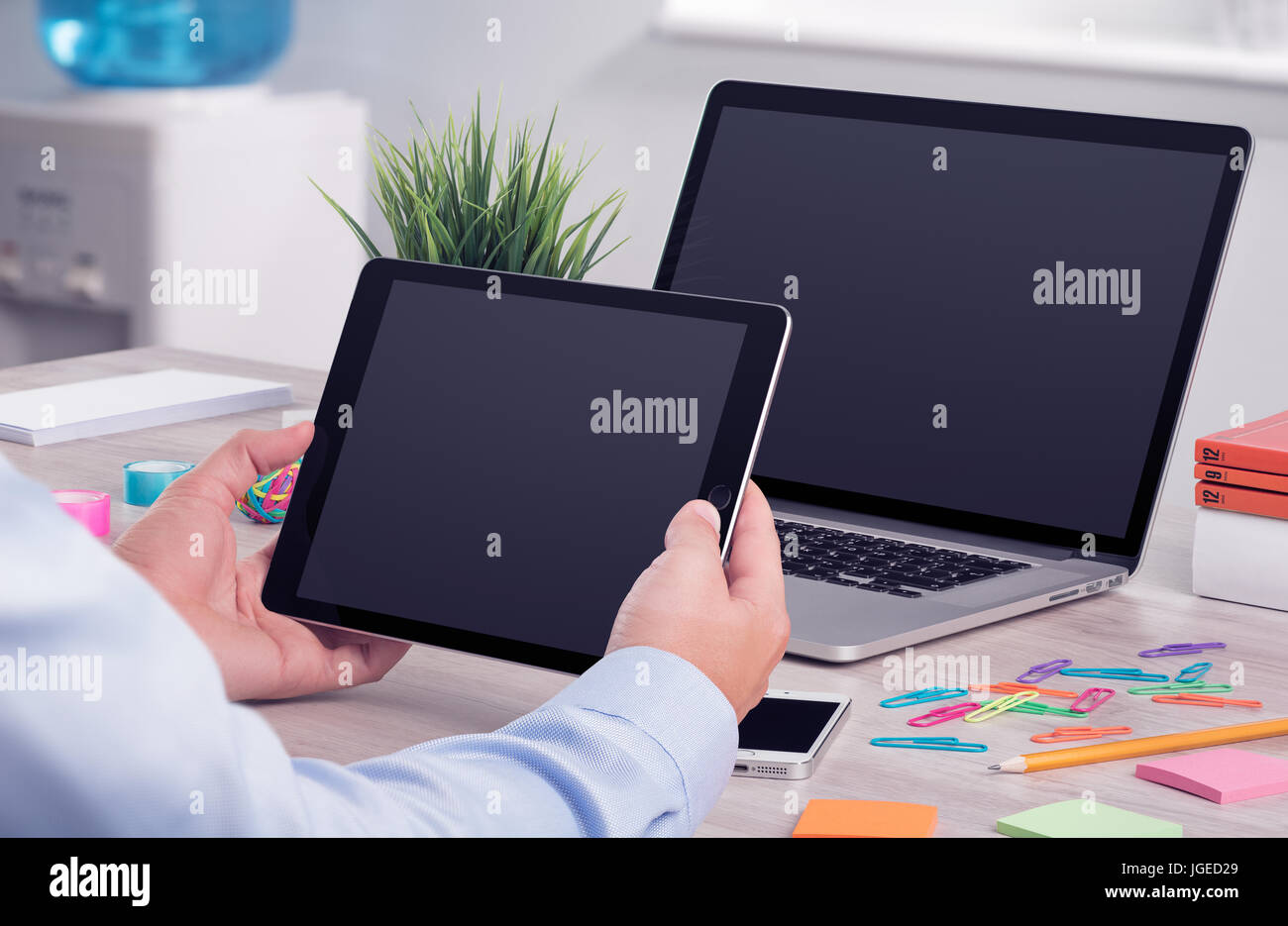 Businessman holding and working with digital tablet pc. Modern office desk workplace with laptop computer mockup Stock Photo
