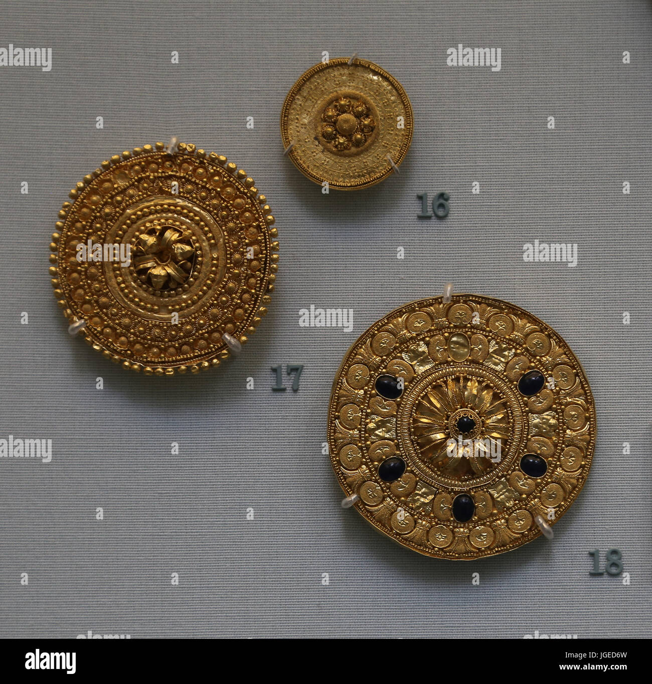 Gold ear-studs with a rosette sorrounted by concentric bands and vitreous glass paste. Etruscan, 530-480 BC. Italy. - Stock Image