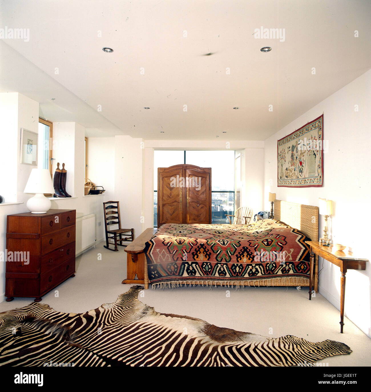 Zebra skin rug in modern bedroom with traditional furniture and a bed covered with a Kelim rug - Stock Image