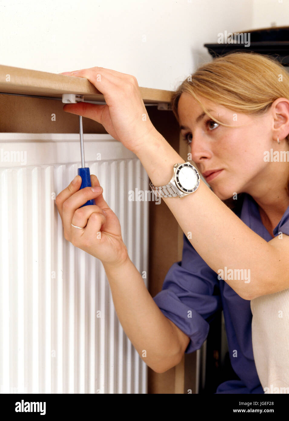 Woman fitting a radiator cover. Step x step craft & DIY projects - Stock Image