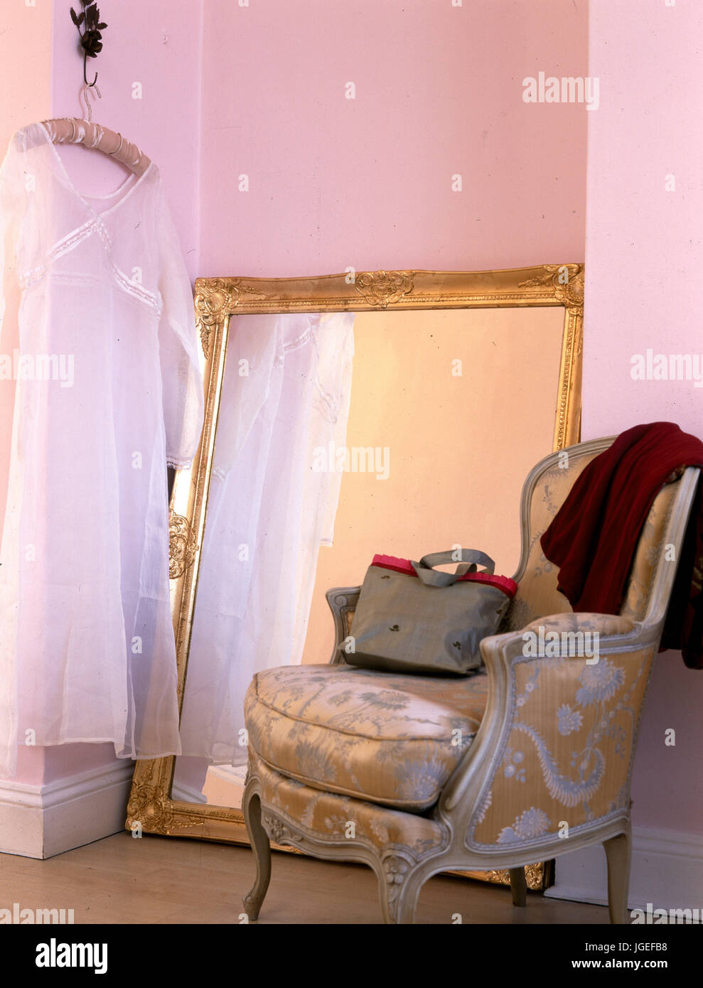 French Style Armchair Beside Large Mirror Leaning Against Wall With