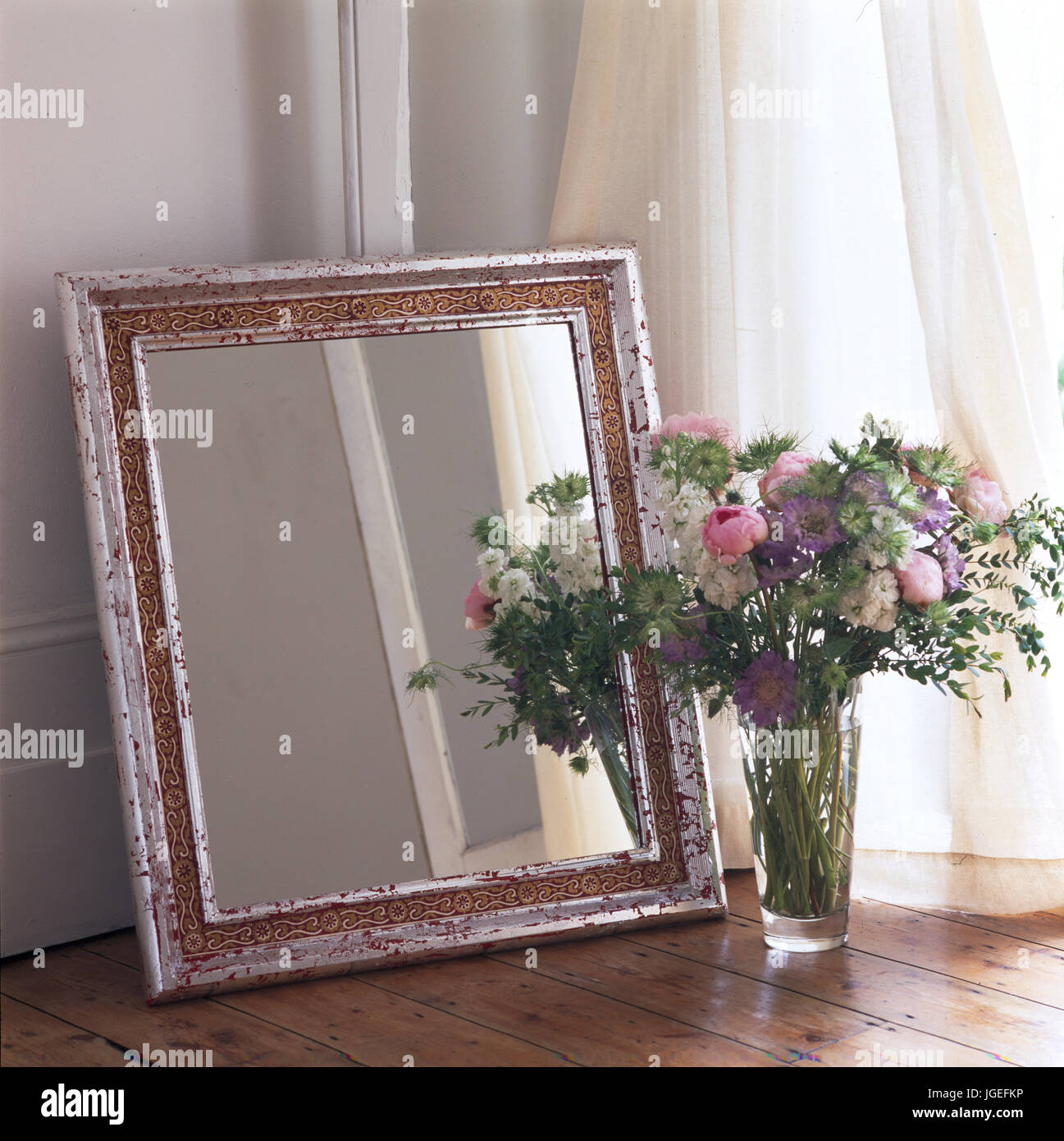 Closeup of free-standing mirror leant against wall with vase of pink and   mauve flowers. - Stock Image