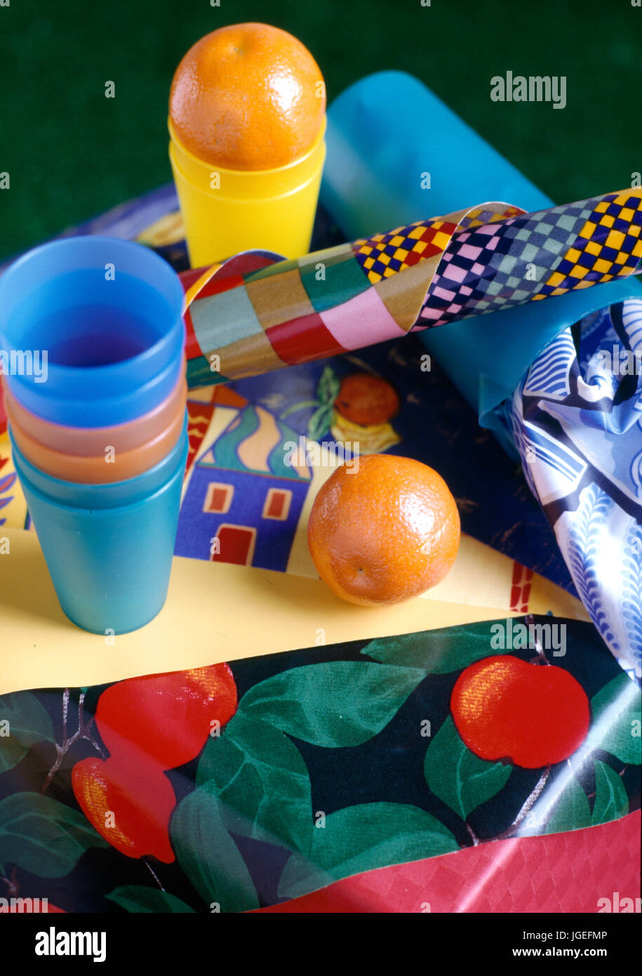 Colouful plastic beakers and fabric samples. - Stock Image