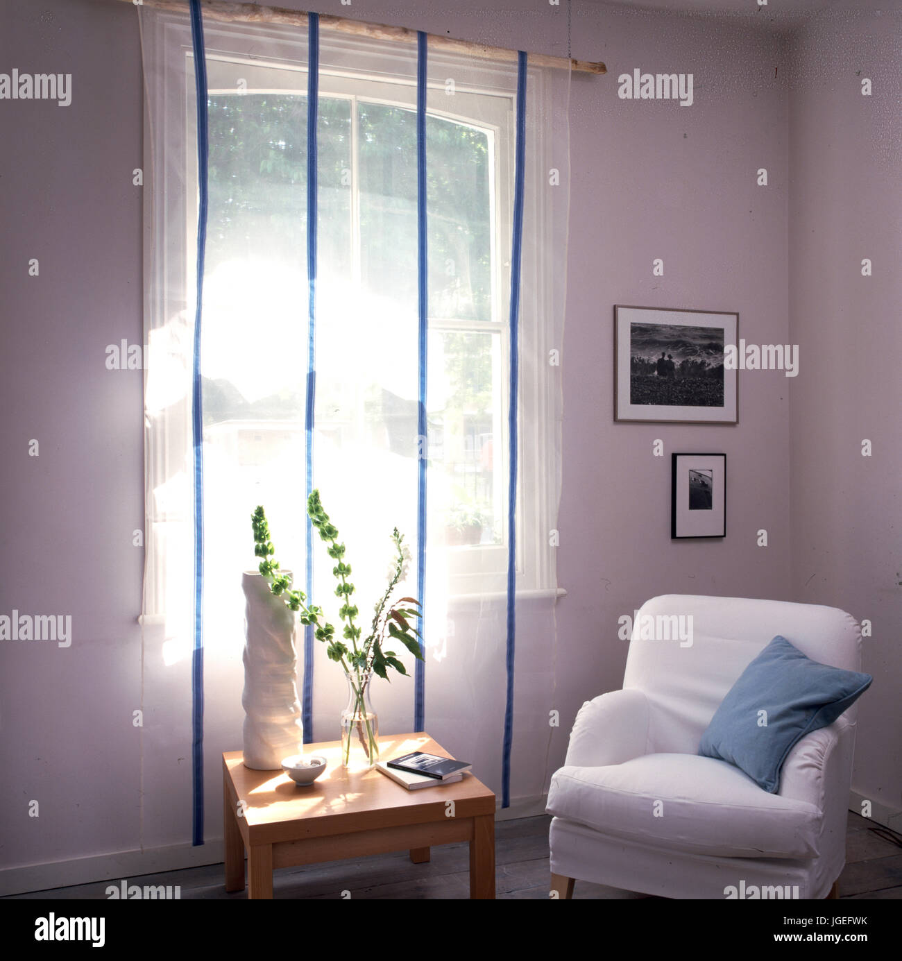 Sheer fabric covering window with blue vertical ribbons - Stock Image
