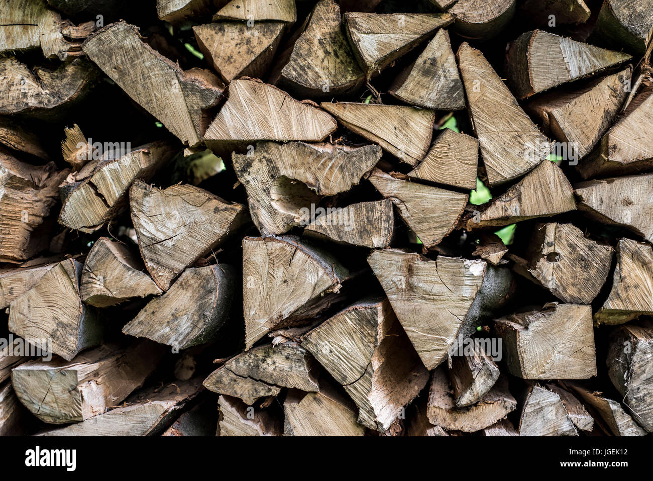 Abstract photo of a pile of natural wooden logs background dry chopped firewood logs ready for winter Stock Photo