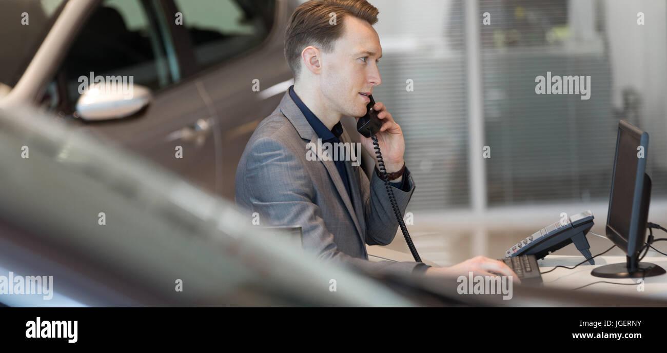 Salesman talking on landline phone in showroom - Stock Image