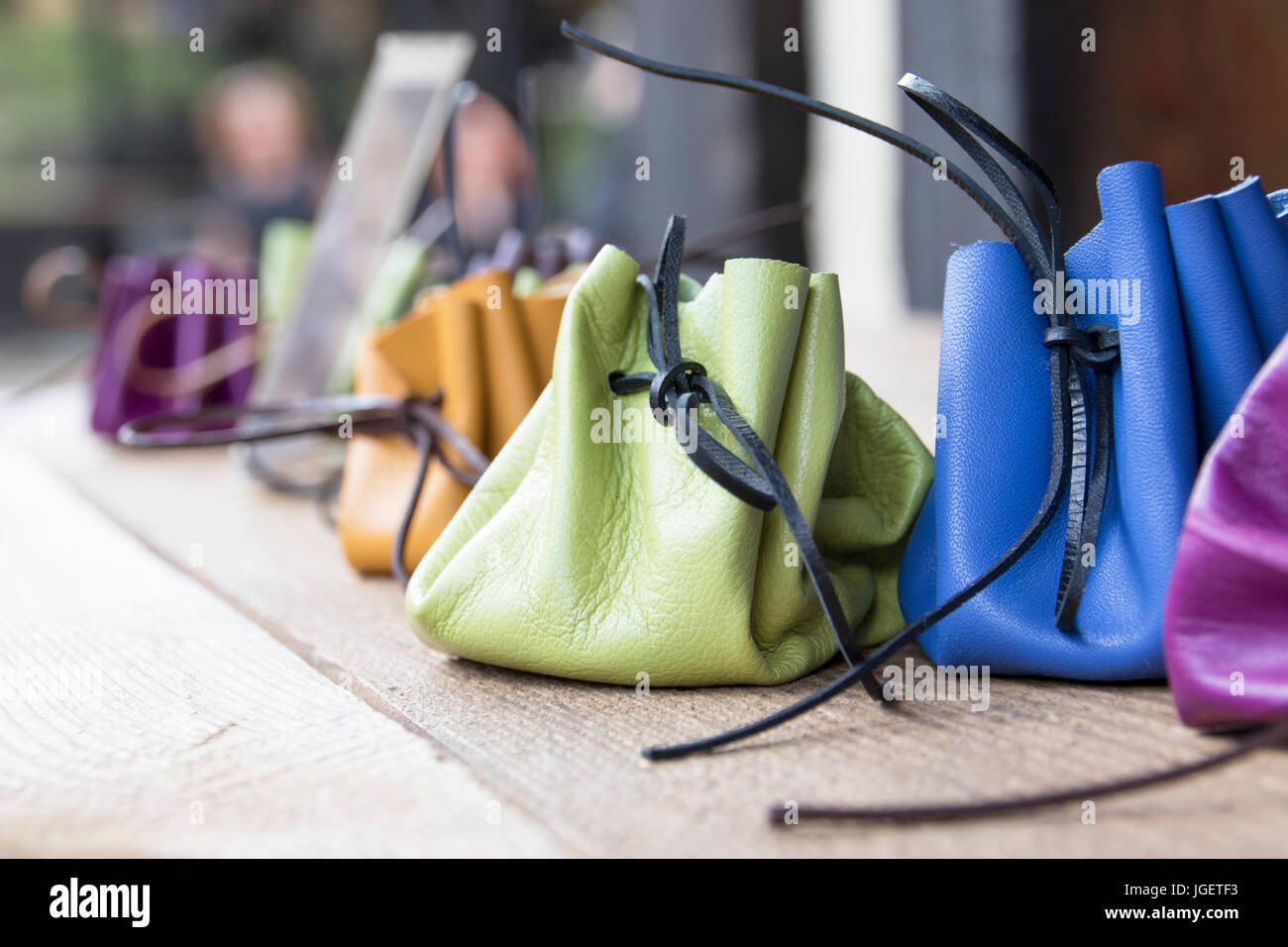 handmade leather purses in bright colors on display in an outdoor market in the Czech Republic - Stock Image