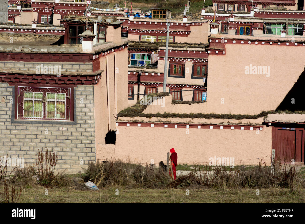 Tibetan monk walking in the colorful city of Litang, Sichuan, China. - Stock Image