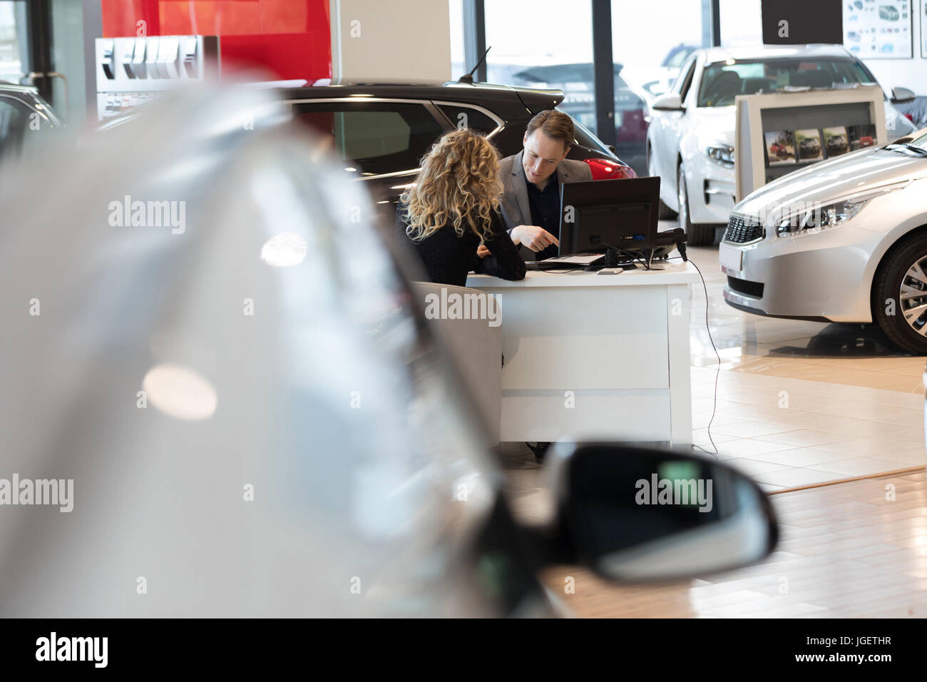 Salesman discussing with customer in car showroom - Stock Image