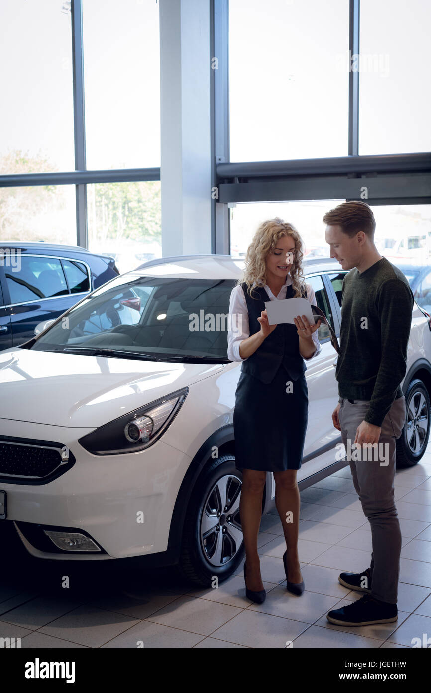 Confident saleswoman showing brochure to customer in car showroom - Stock Image
