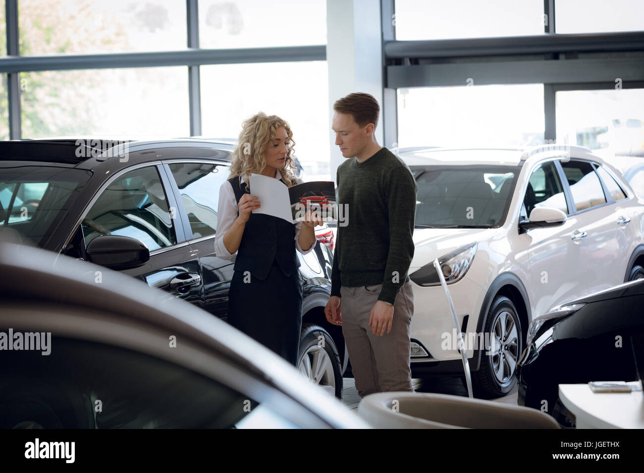 Saleswoman showing brochure to male customer - Stock Image
