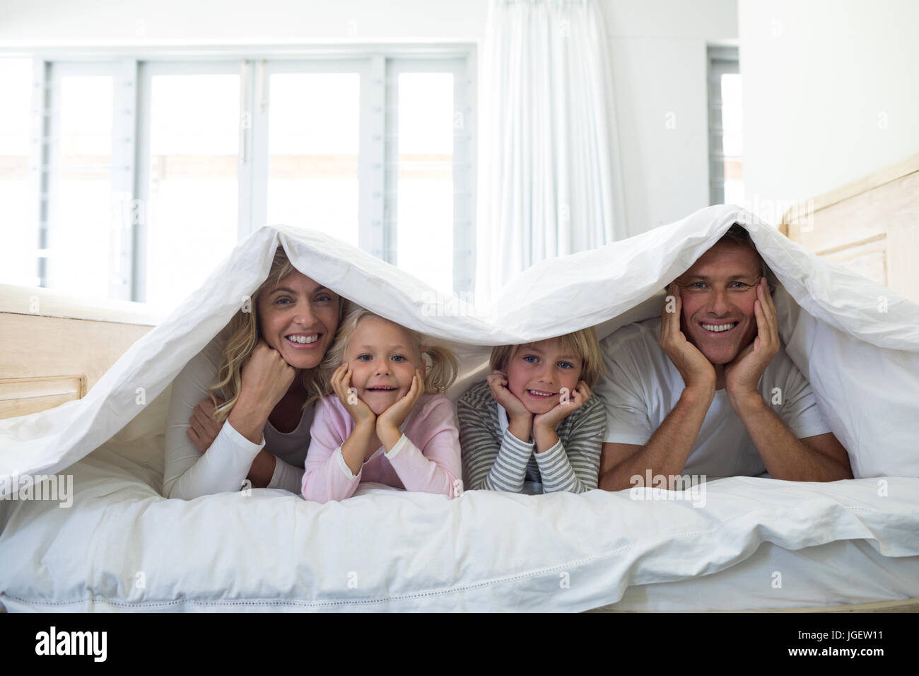 Portrait Of Happy Family Lying Under Blanket On Bed In Bedroom At Stock Photo Alamy