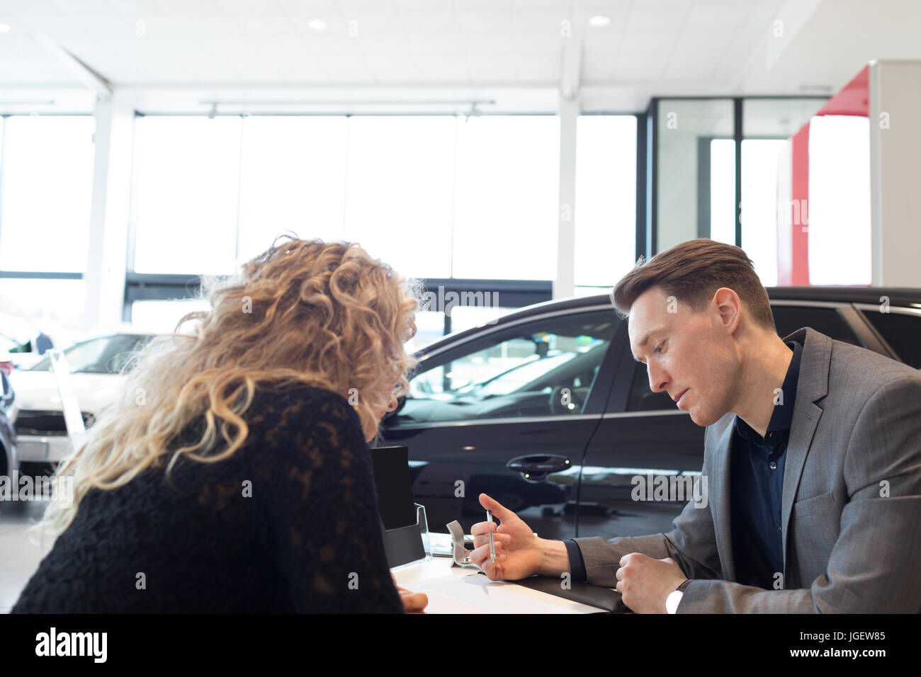 Salesman discussing over document with customer in showroom - Stock Image