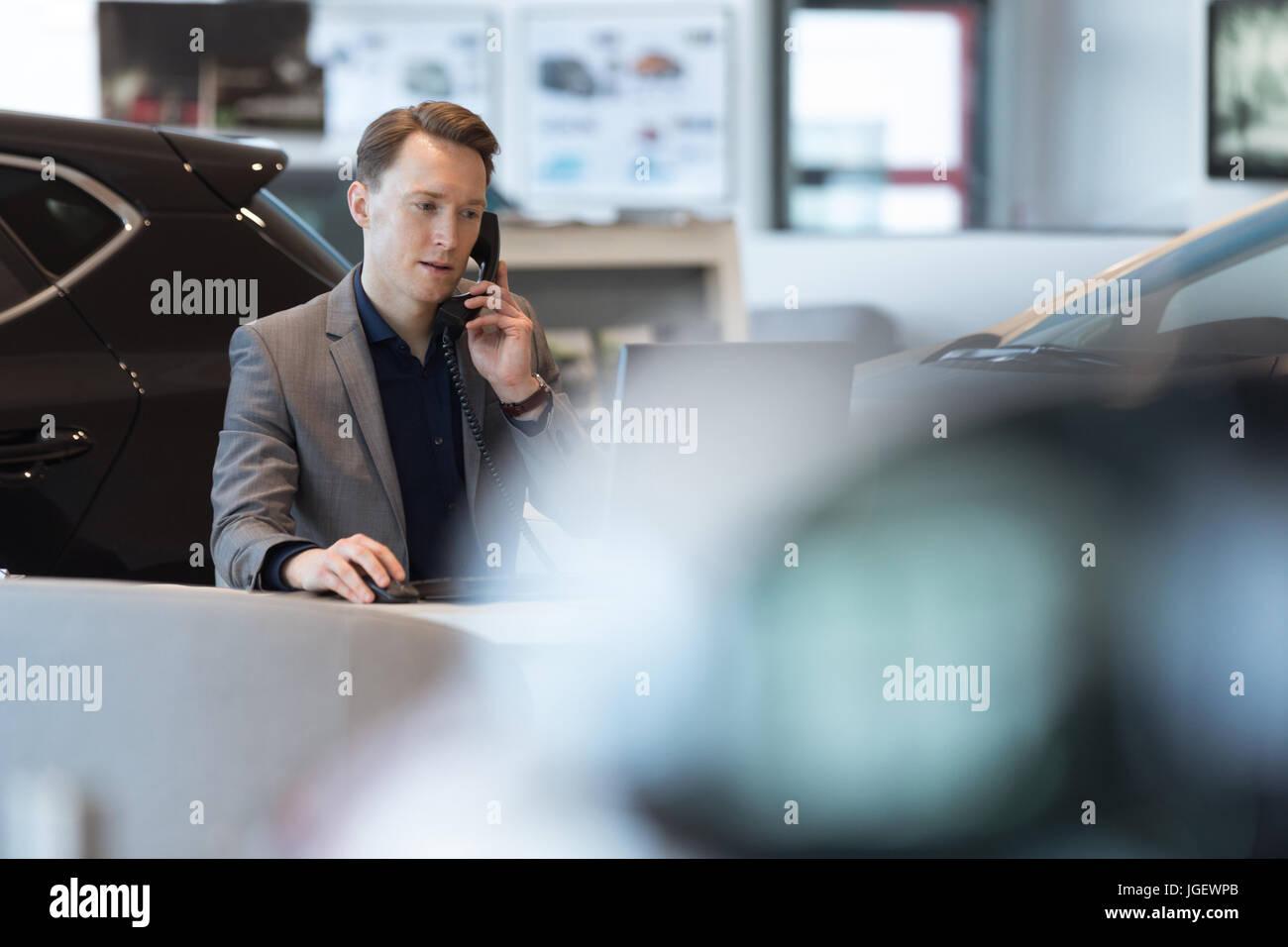 Car salesperson talking on landline phone - Stock Image