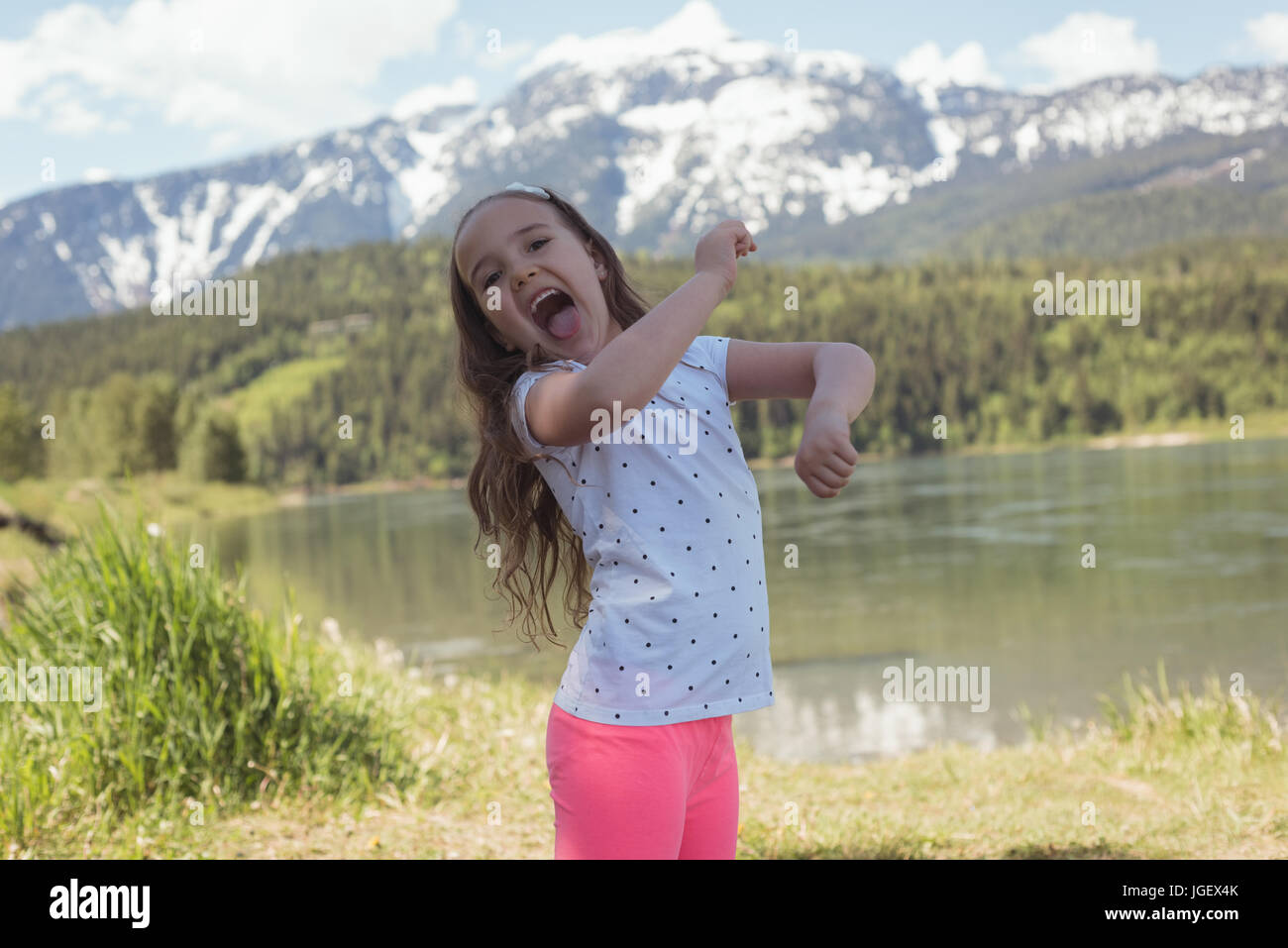 Portrait of cute girl having fun near river on a sunny day - Stock Image