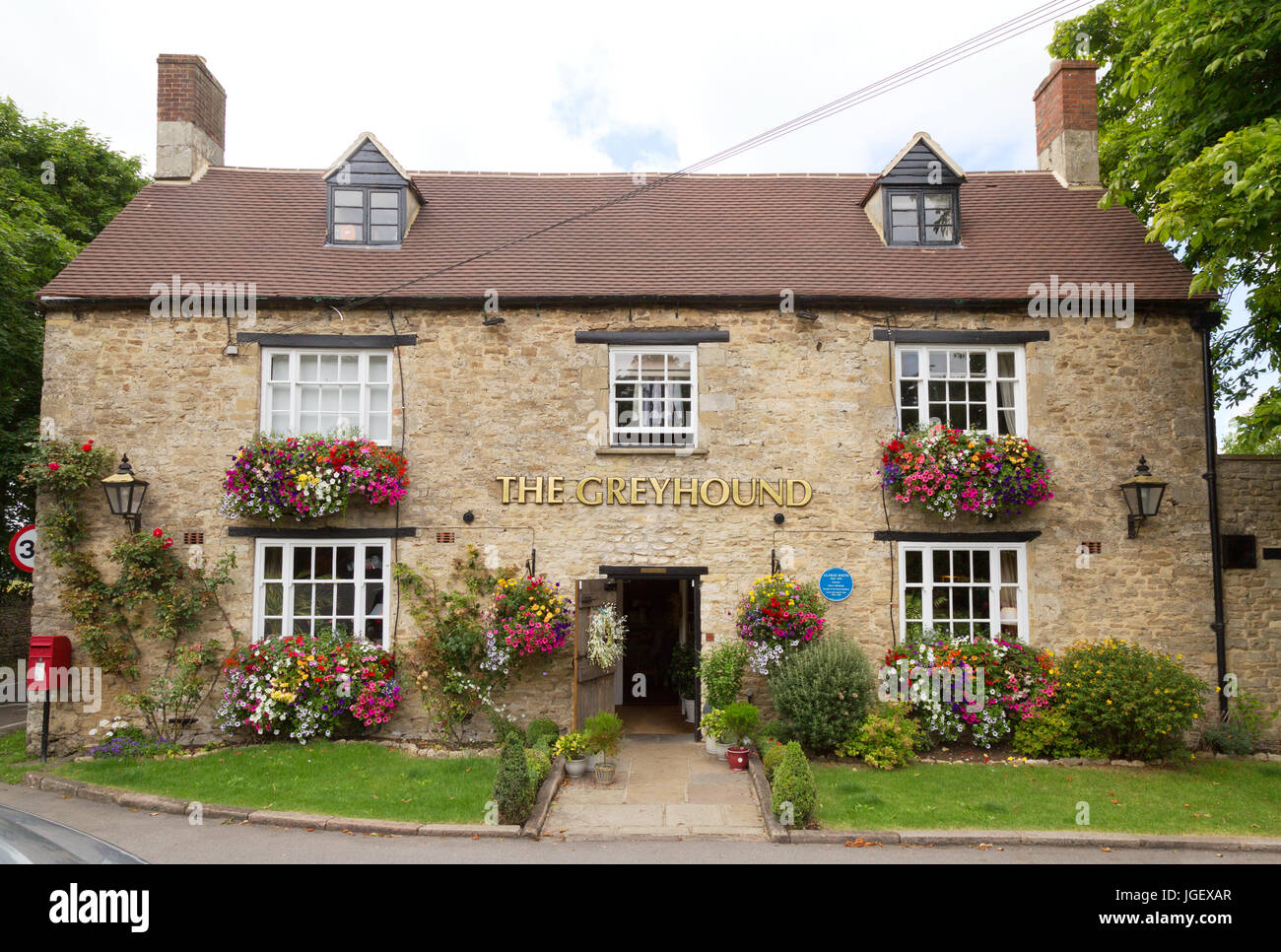 The Greyhound Pub, Wooton, Oxfordshire in summer with flowers and hanging baskets; Oxfordshire England UK - Stock Image