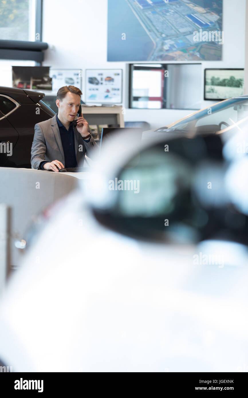 Car salesperson talking on landline phone in car showroom - Stock Image
