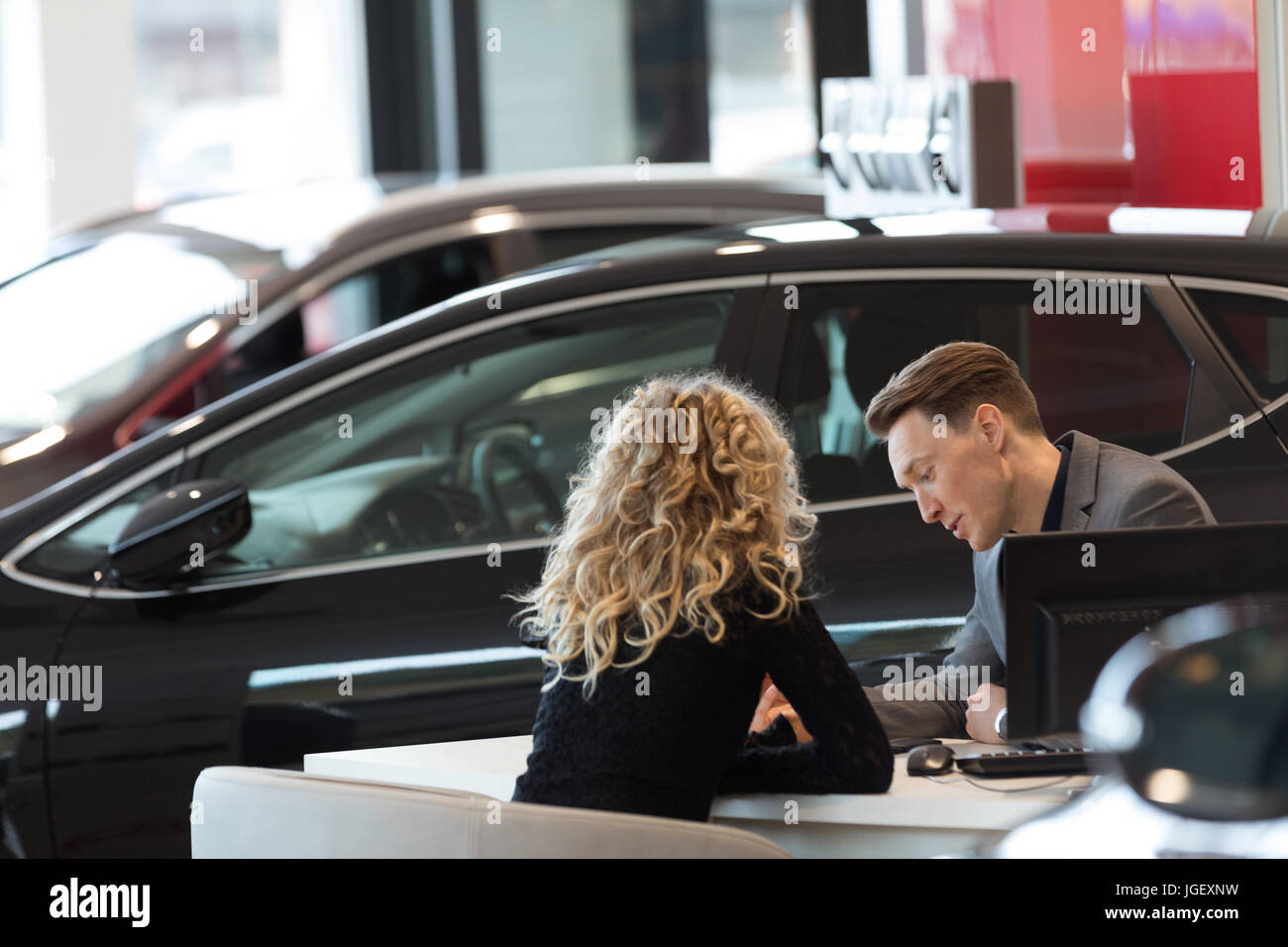Car salesperson discussing with customer in showroom - Stock Image