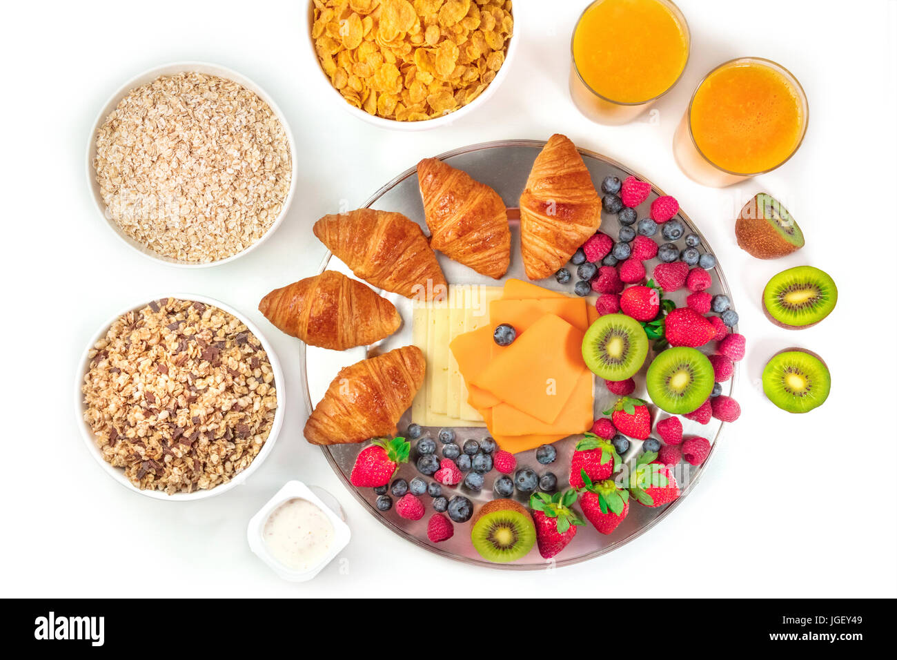 Overhead photo of a continental hotel breakfast on white background. An assortment of croissants, cheese, fresh - Stock Image