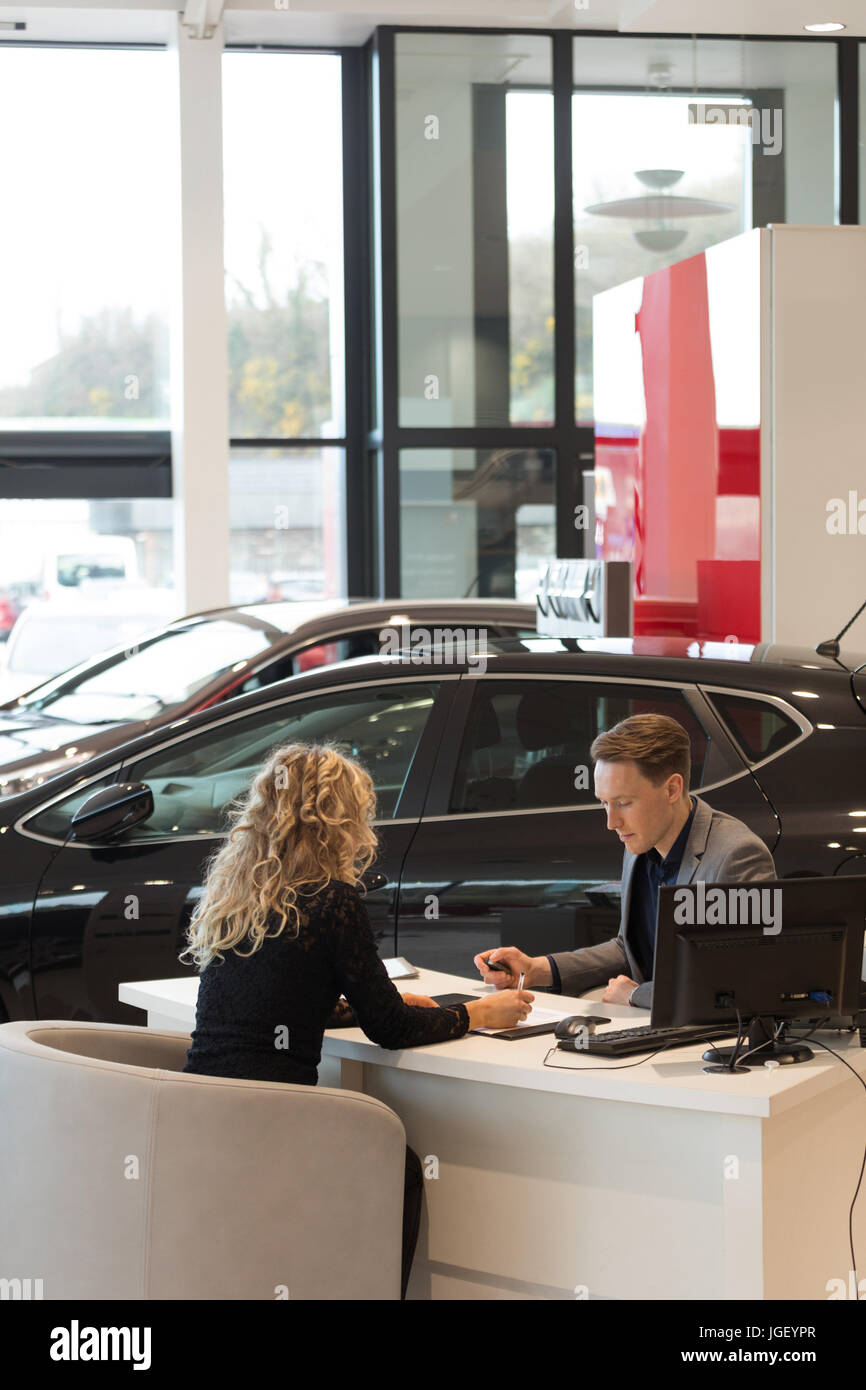 Female customer discussing with salesman in carshowroom - Stock Image