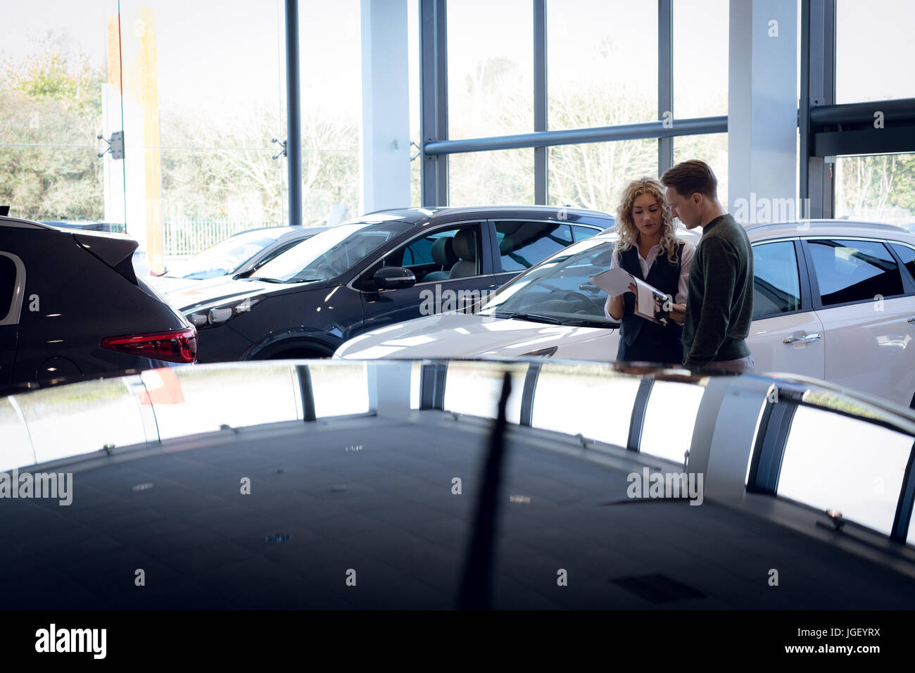 Saleswoman discussing over brochure with customer in showroom - Stock Image
