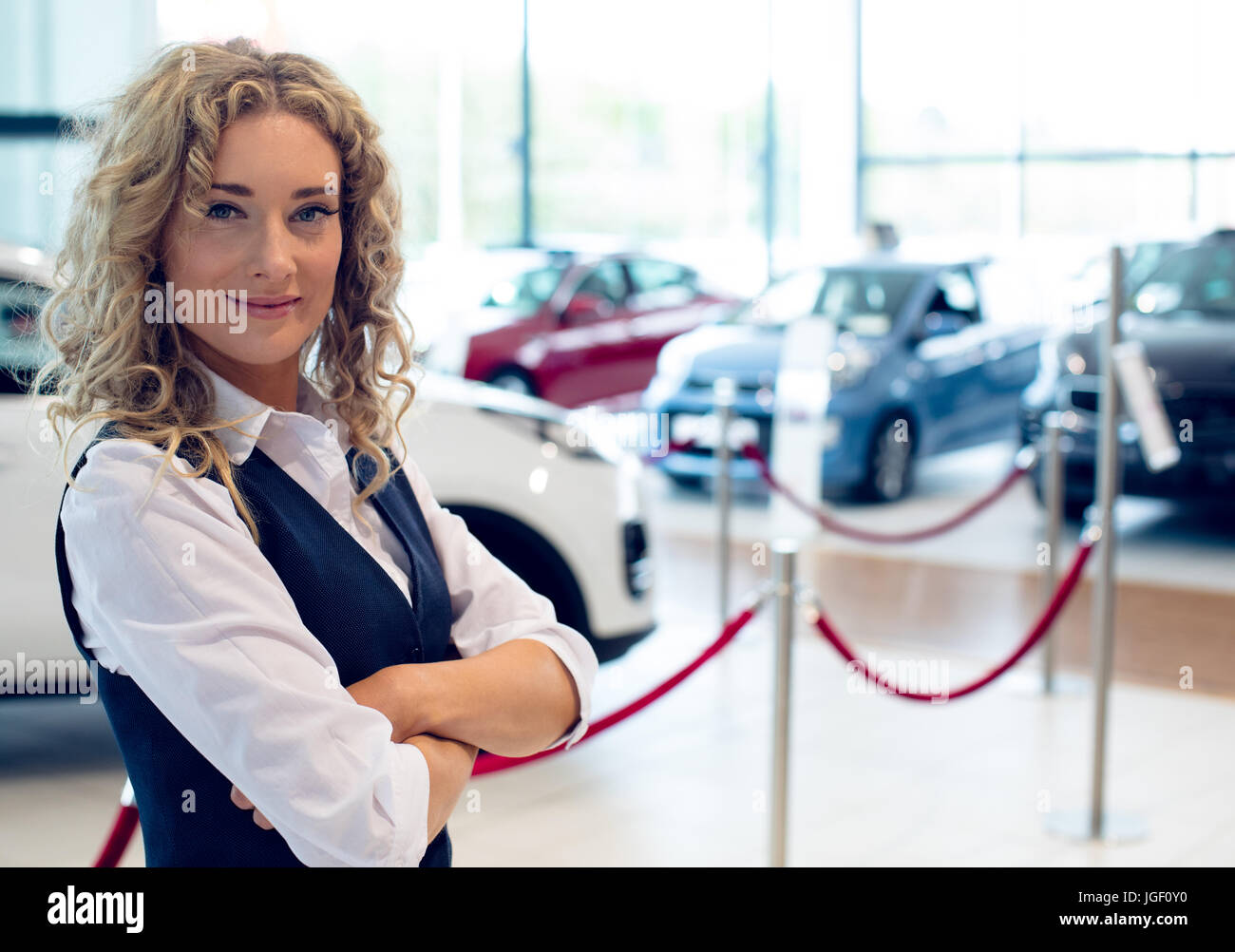 Portrait of smiling saleswoman standing in showroom - Stock Image