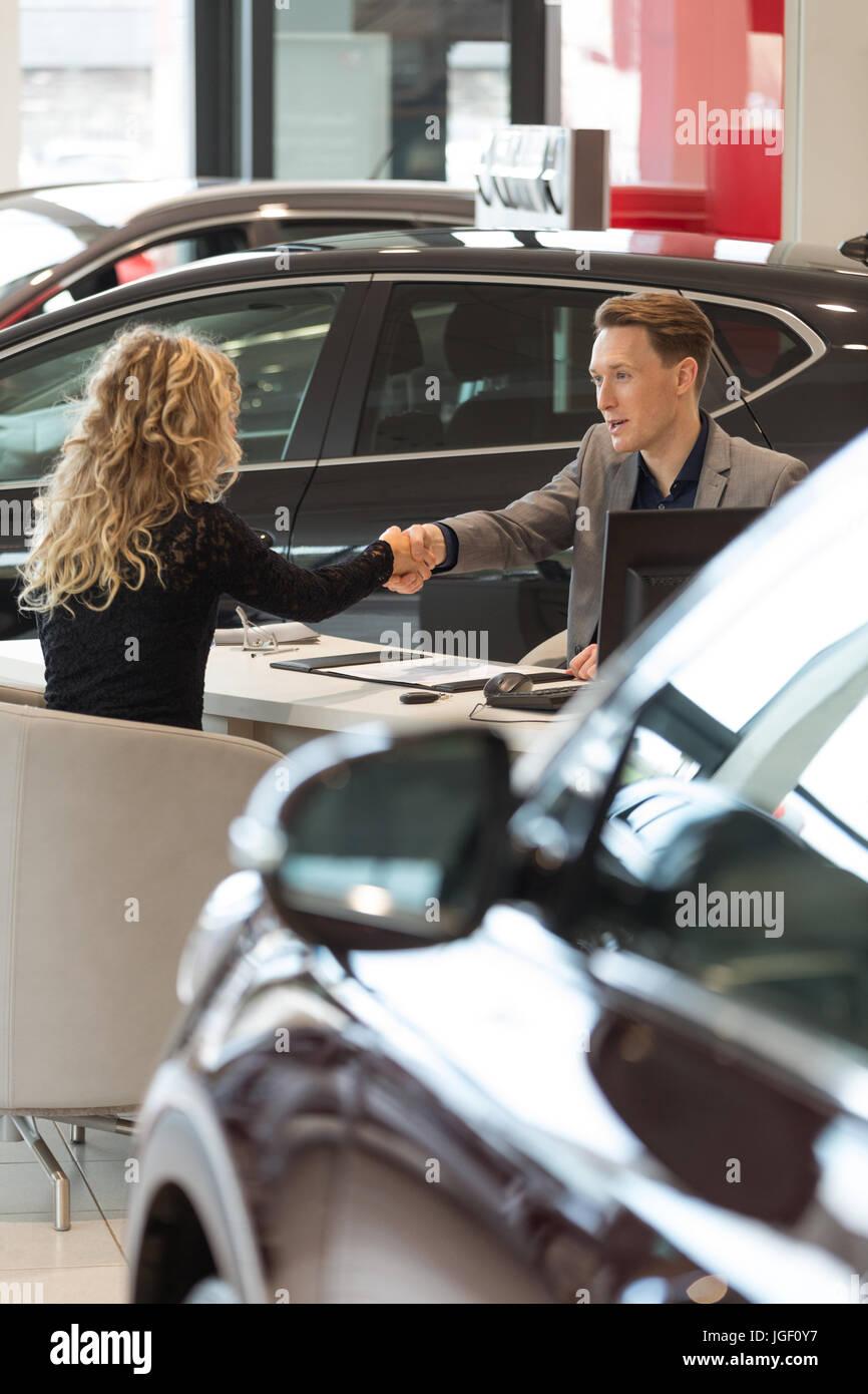 Salesman doing handshake with female customer - Stock Image