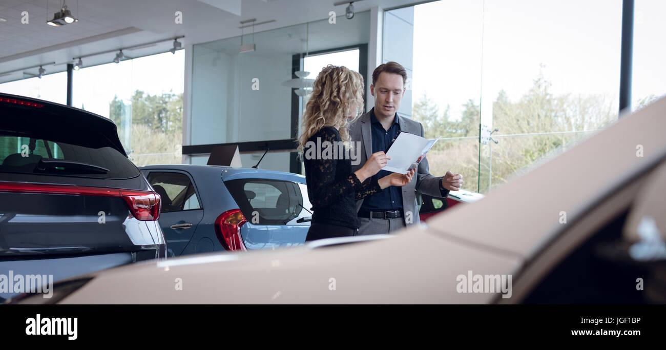 Female customer showing brochure to salesman in showroom - Stock Image