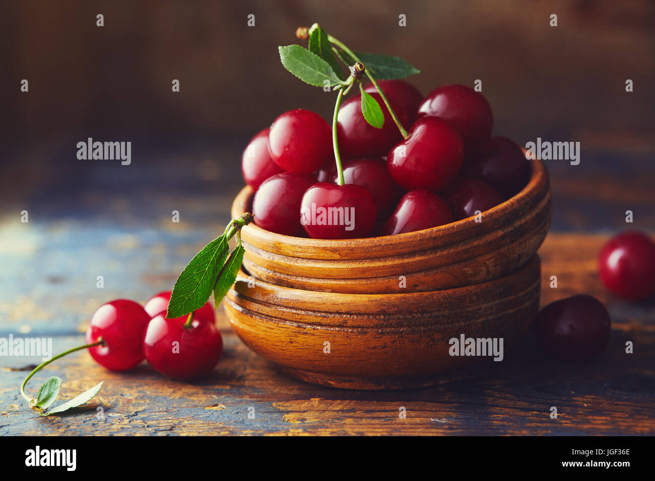 Cherries in a bowl on a wooden table. Freshly harvested cherries in a bowl on a wooden table. - Stock Image