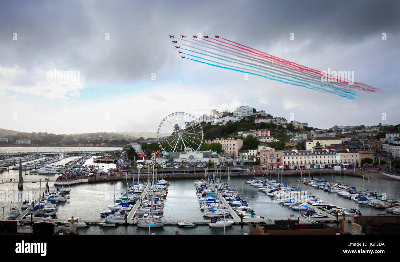 The Red Arrows perform a colourful display over the English Riviera at Torquay, Devon, UK - Stock Image