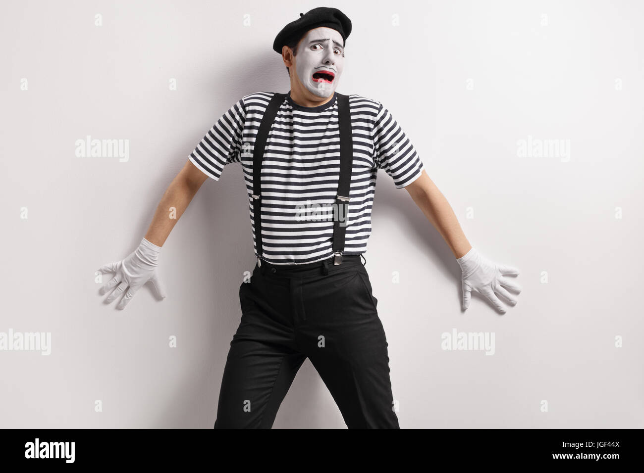 Terrified mime against a wall - Stock Image