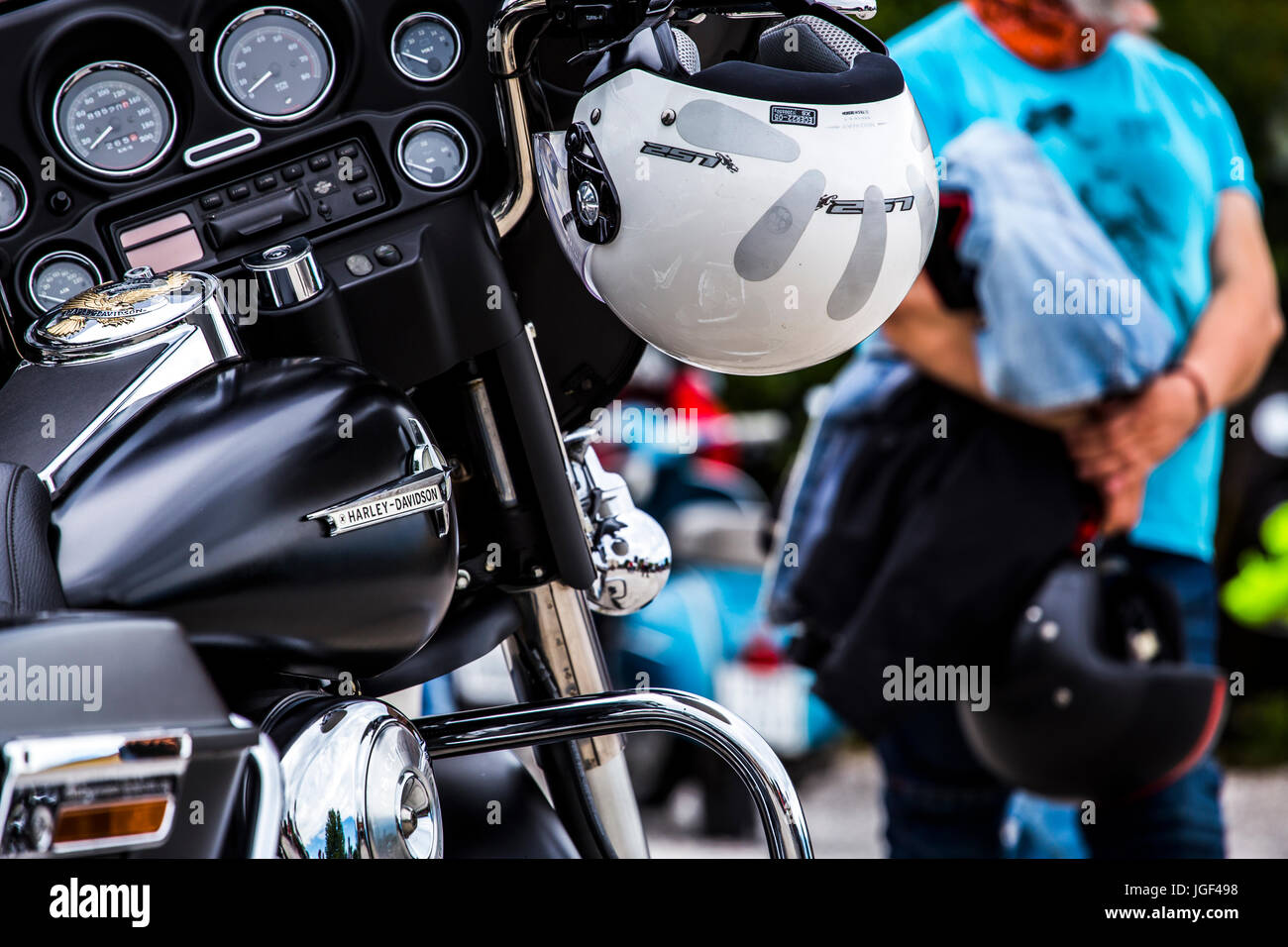 White helmet hanging on the handlebar of a Harley Davidson Electra Glide. - Stock Image