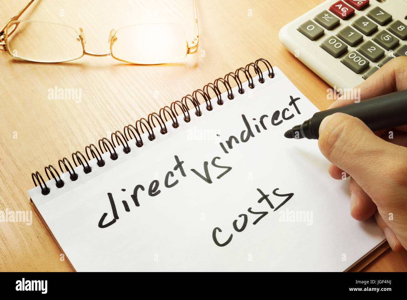 Direct vs indirect costs written by hand in a note. - Stock Image