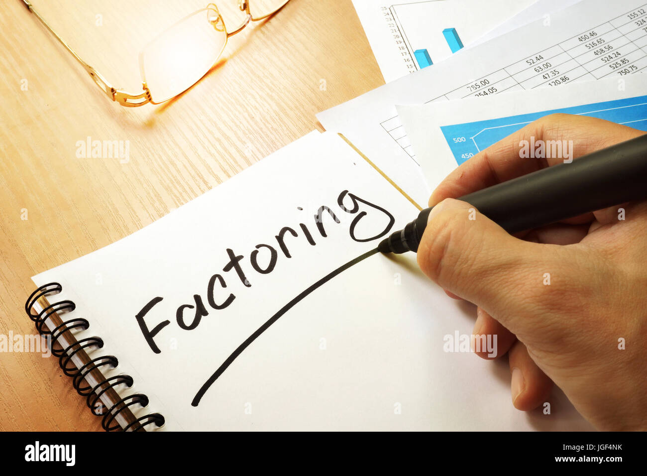 Factoring written by hand in a note. - Stock Image