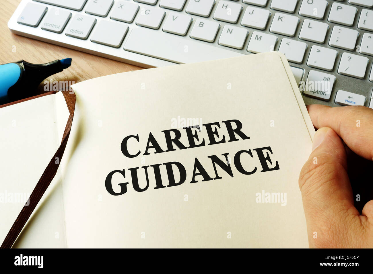Hands holding book with title career guidance. - Stock Image