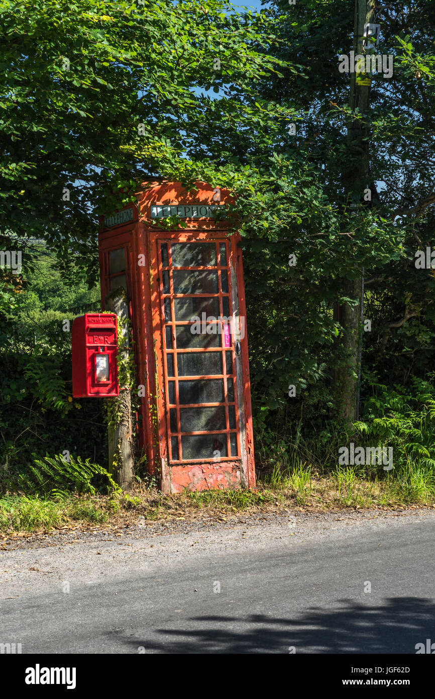 Old red telephone box and red letter posting box on country / rural road in Cornwall, UK. Box and telegraph pole - Stock Image