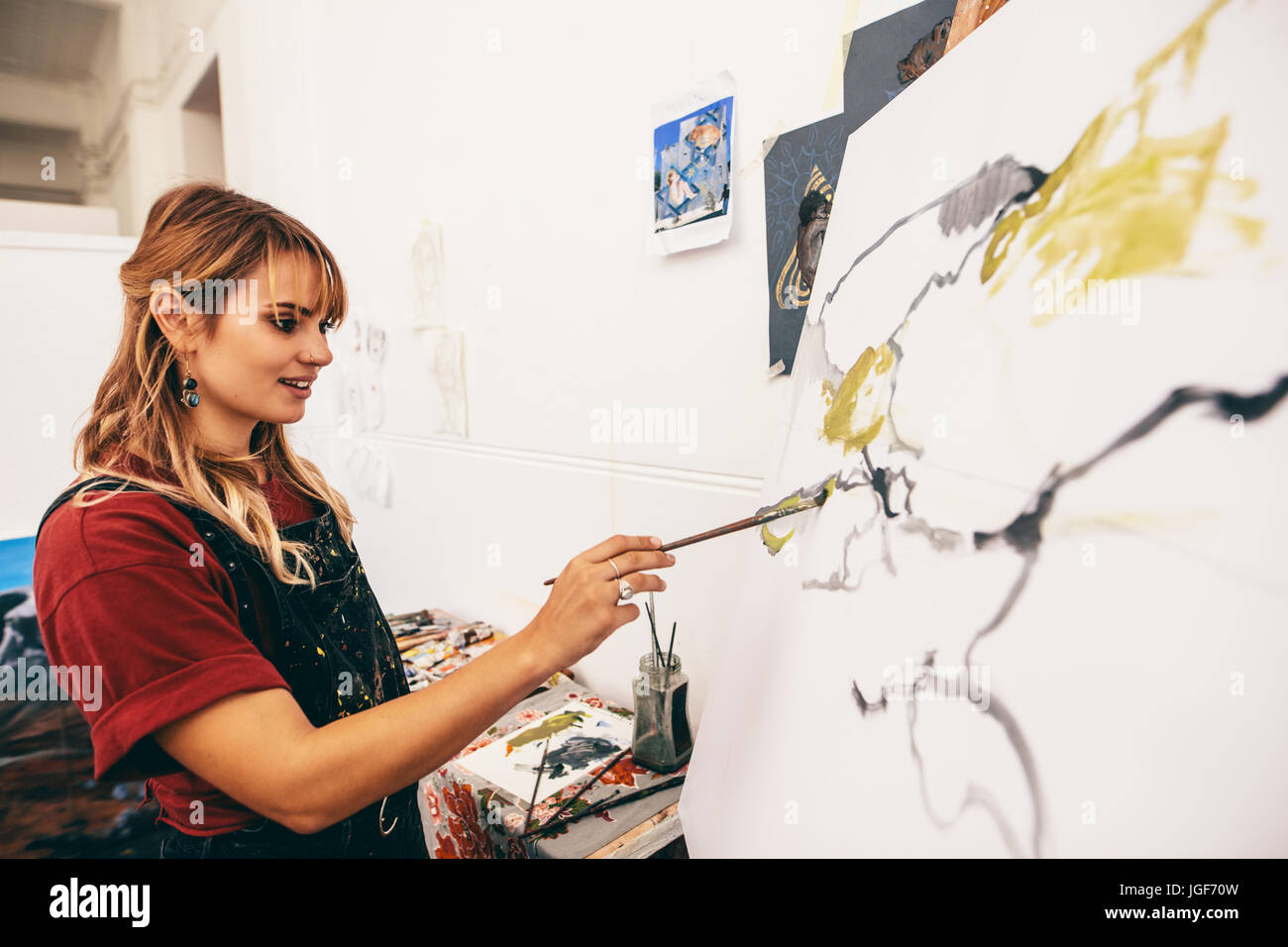 Creative female painter paints a colorful picture on canvas in workshop. Woman artist making a painting in her studio. - Stock Image